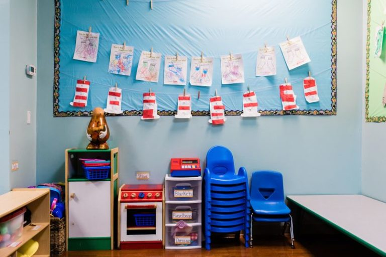 Very organized nursery room with blue chairs, wooden and plastic cabinets and a bed at a Childcare Serving Branford, Cheshire, Wallingford, CT