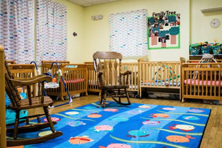 Nursery room with rocking chairs with cribs without babies at a Childcare Serving Branford & Wallingford, CT